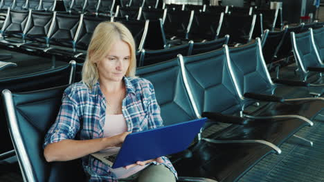 A-Woman-Uses-A-Laptop-In-An-Airport-Lounge-Leisure-Pending-Flight