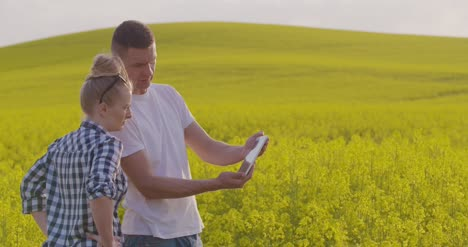 Scientists-Photographing-Rapeseed-Through-Digital-Tablet-While-Discussing-At-Farm