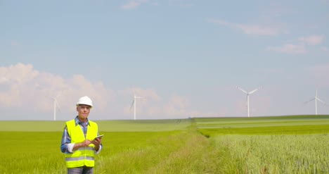 Engineer-Using-Digital-Tablet-On-Wind-Turbine-Farm-10