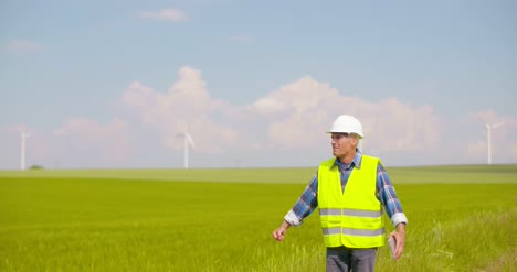 Engineer-Using-Digital-Tablet-On-Wind-Turbine-Farm-12