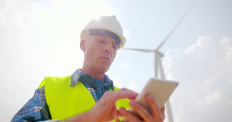 Engineer-Using-Digital-Tablet-On-Wind-Turbine-Farm-13