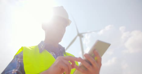 Smiling-Engineer-Using-Digital-Tablet-At-Windmill-Farm-Against-Sky-14