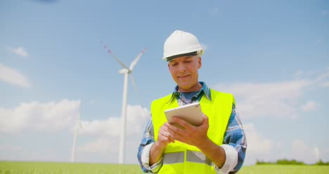 Engineer-Using-Digital-Tablet-On-Wind-Turbine-Farm-2