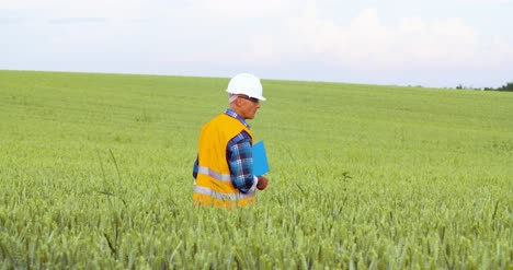 Engineer-Analyzing-Checklist-On-Clipboard-Amidst-Crops-At-Farm-2