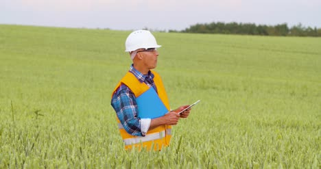 Engineer-Analyzing-Traffic-Polution-On-Clipboard-Amidst-Crops-At-Farm