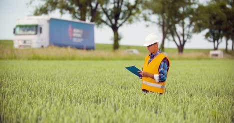 Engineer-Analyzing-Traffic-Polution-On-Clipboard-Amidst-Crops-At-Farm-6