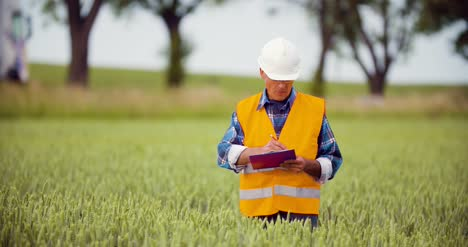Engineer-Analyzing-Traffic-Polution-On-Clipboard-Amidst-Crops-At-Farm-7