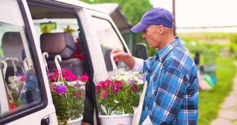 Male-Farmer-Loading-Van-Trunk-With-Hanging-Plants-2