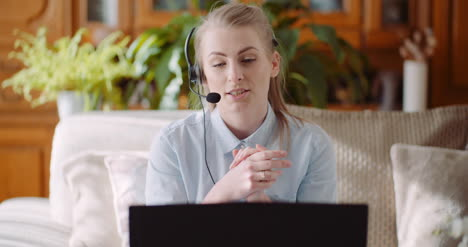 Sales-Representative-In-Headset-Speaking-To-Client-And-Making-Video-Conference-Call-On-Laptop-
