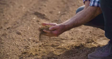 Farmer-Hands-Holding-And-Pouring-Back-Organic-Soil