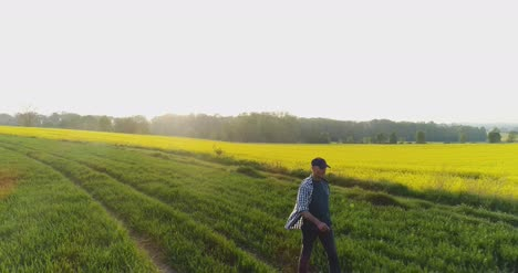 Farmer-Walking-On-Farm-With-Digital-Tablet-At-Golds-Sunset