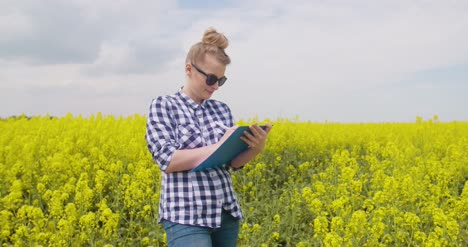 Confident-Female-Farmer-Writing-In-Clipboard-At-Rapeseed-Field-14