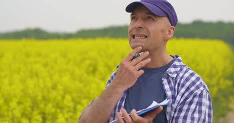 Thoughtful-Scientist-Writing-In-Clipboard-At-Rapeseed-Field