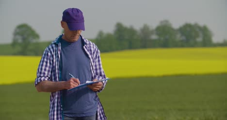 Mature-Farmer-Writing-In-Clipboard-At-Rapeseed-Cultivated-Field-1