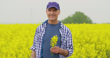 Portrait-Of-Happy-Farmer-Holding-Rapeseed-Blossoms-At-Farm