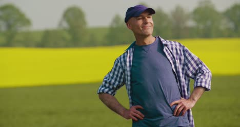 Smiling-Mature-Farmer-Examining-Agricultural-Field-1