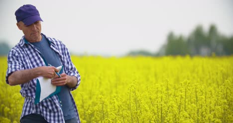 Mature-Farmer-Writing-In-Clipboard-At-Rapeseed-Cultivated-Field-7