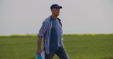 Mature-Farmer-Writing-In-Clipboard-At-Rapeseed-Cultivated-Field-9
