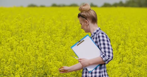 Confident-Female-Farmer-Writing-In-Clipboard-At-Rapeseed-Field-17