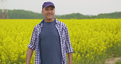 Happy-Male-Farmer-Celebrating-Success-At-Rapeseed-Field