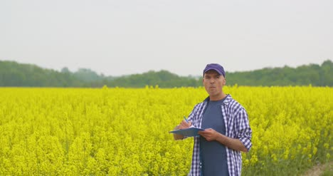 Mature-Farmer-Writing-In-Clipboard-At-Rapeseed-Cultivated-Field-10
