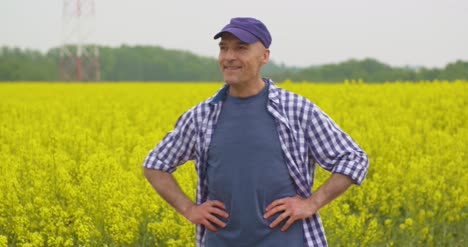 Happy-Farmer-With-Hands-Clasped-Standing-At-Rapeseed-Field