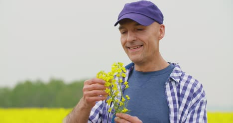Portrait-Of-Happy-Farmer-Holding-Rapeseed-Blossoms-At-Farm-2