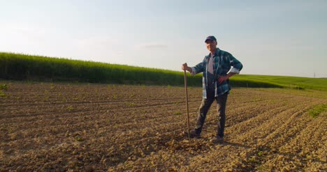 Successful-Farmer-Holding-Hoe-At-Farm-Agriculture