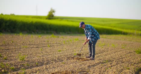Farmer-Using-Hoe-On-Dirt-At-Farm