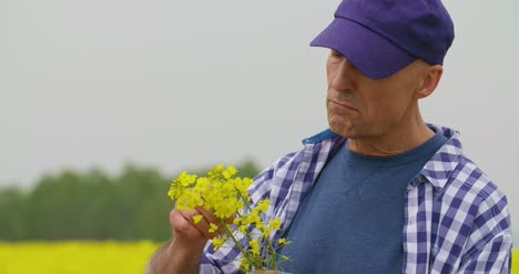 Portrait-Of-Happy-Farmer-Holding-Rapeseed-Blossoms-At-Farm-3