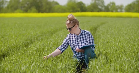 Researcher-Examining-Crops-While-Writing-In-Clipboard-2
