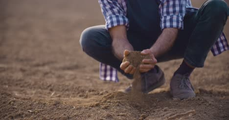 Hands-Examining-Soil-In-Agricultural-Field-8