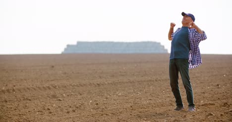 Tired-Farmer-Stretching-While-Walking-In-Farm-3