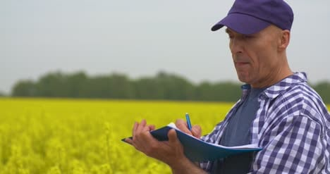 Scientist-Thinking-And-Writing-In-Clipboard-At-Rapeseed-Field