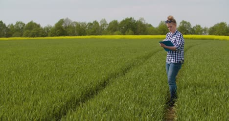 Researcher-Examining-Crops-While-Writing-In-Clipboard-4