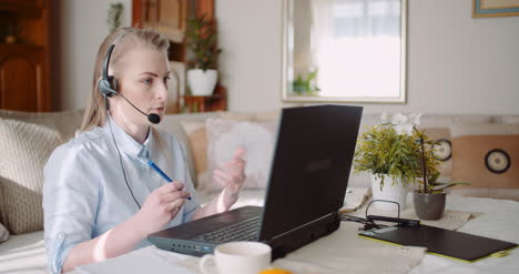 Sales-Representative-In-Headset-Speaking-To-Client-And-Making-Video-Conference-Call-On-Laptop-10