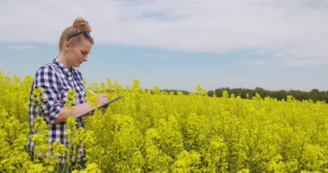 Confident-Female-Farmer-Writing-In-Clipboard-At-Rapeseed-Field-3