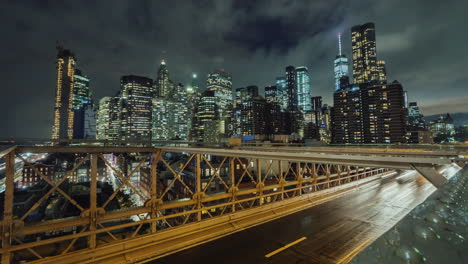 Traffic-Over-The-Famous-Brooklyn-Bridge-At-Night-Against-The-Backdrop-Of-The-Skyscrapers-Of-Manhatta