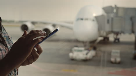 Woman-s-Hands-With-A-Smartphone-Writes-A-Message-On-The-Background-Of-The-Airliner-Outside-The-Airpo