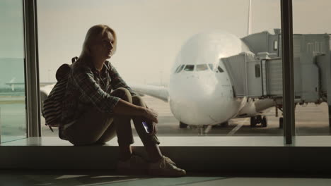 A-Single-Woman-Is-Sitting-On-The-Windowsill-In-The-Airport-Terminal-Amid-A-Huge-Airliner-Loneliness-