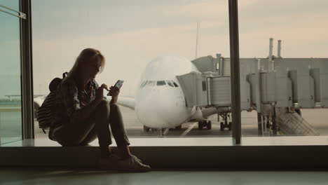 Active-Girl-Tourist-With-A-Backpack-Sits-On-The-Window-In-The-Background-Of-The-Aircraft-And-Plays-O