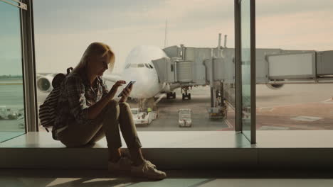 A-Female-Passenger-Sits-On-The-Windowsill-In-The-Airport-Terminal-Uses-A-Smartphone-Against-The-Back