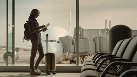 Silhouette-Of-A-Woman-With-Boarding-Documents-Standing-At-The-Terminal-Window-Outside-The-Window-A-B