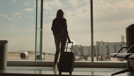 A-Woman-With-Luggage-Goes-To-A-Large-Window-In-The-Airport-Terminal-Outside-The-Window-You-Can-See-A