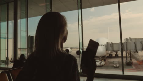 Joyful-Woman-With-Documents-In-Hand-Goes-To-The-Window-Where-You-Can-See-A-Large-Airliner-In-Anticip