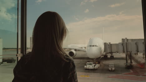 Silhouette-Of-A-Young-Woman-Looking-Through-A-Large-Window-On-An-Airliner