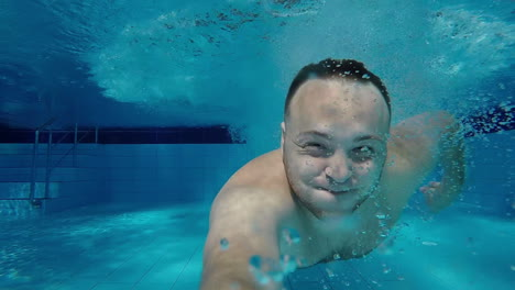 A-Man-Swims-Under-The-Water-In-The-Pool-With-His-Eyes-Open-Looking-Into-The-Camera-Underwater-Selfie