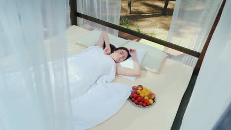 A-Young-Woman-Wakes-Up-On-A-Lounger-Covered-With-Curtains-Near-Her-A-Plate-Of-Fruit-Gorgeous-Romanti