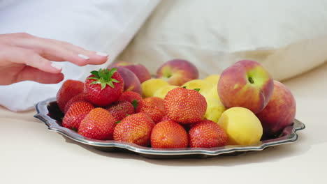 A-Woman-s-Hand-Chooses-A-Delicious-Fruit-The-Plate-Stands-Near-The-Pillow---Breakfast-In-Bed-And-The