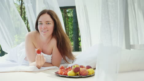 Young-Woman-In-Bed-With-A-Strawberry-In-Her-Hand-Lies-By-The-Pool-On-A-Lounger-With-Curtains-Romance